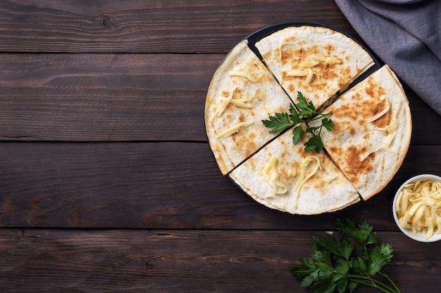 Pedaços de quesadilla com creme de leite cogumelos e queijo em um prato com folhas de salsa.