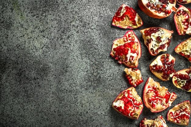 Pedaços de romãs maduras frescas. em fundo rústico