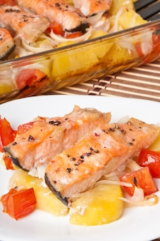 Pedaços de salmão com batatas, tomate e cebola assados no forno