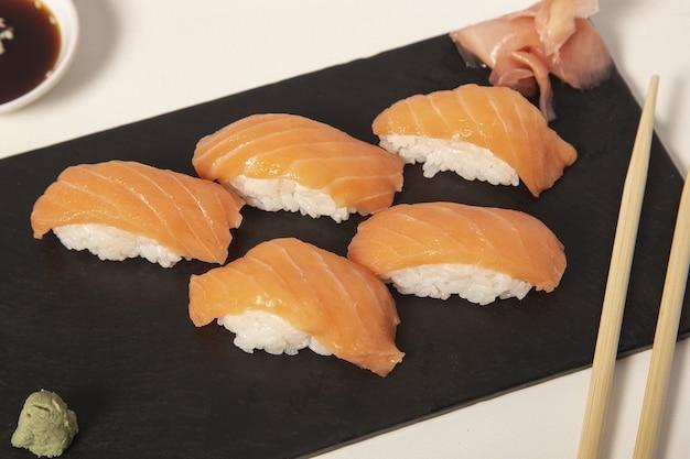 Pedaços de sushi lado a lado em uma superfície preta
