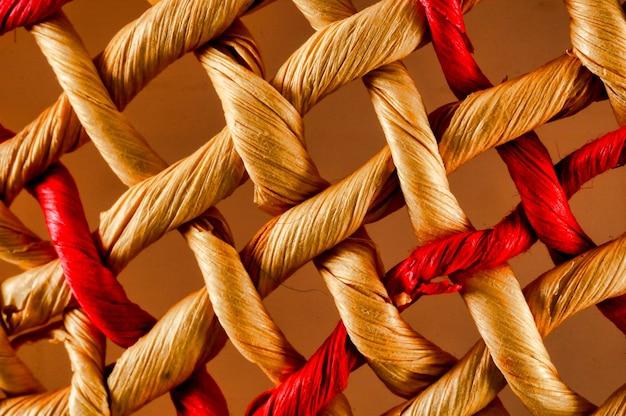 Pedaços de tecido vermelho e amarelo dispostos em um padrão de rede
