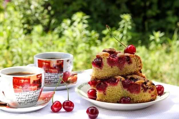 Pedaços de torta com cereja e duas xícaras de café em uma mesa ao ar livre, foto horizontal