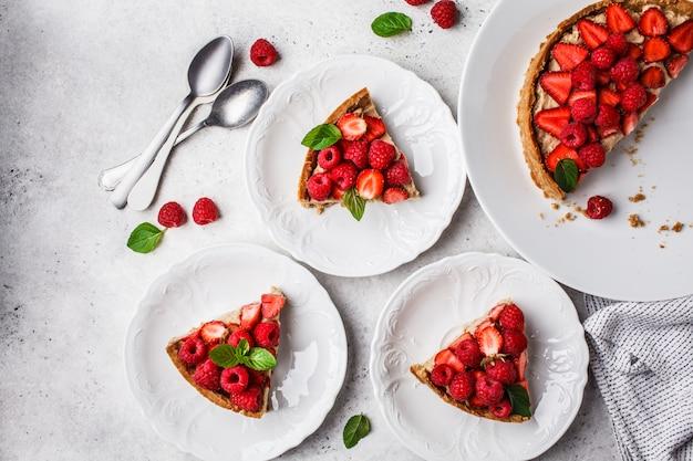 Pedaços de torta de berry com framboesas, morangos e creme