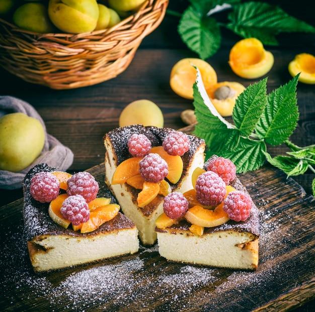 Pedaços de torta de queijo cottage com morangos e damascos