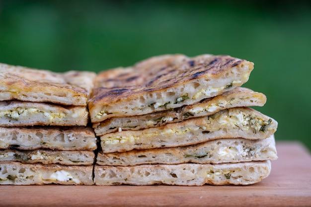 Pedaços de tortilha de massa assada com queijo cottage e ervas em uma mesa de madeira, close-up, prato tradicional turco