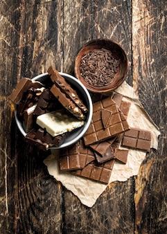 Pedaços de um tipo diferente de chocolate com lascas em uma tigela na mesa de madeira.