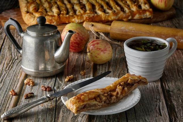 Pedaços de uma deliciosa torta caseira com maçãs e nozes em um prato branco, maçãs e nozes, um bule vintage, uma xícara de chá de ervas e um rolo de massa em uma velha mesa de madeira