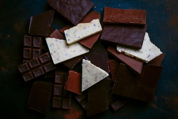 Pedaços escuros, brancos e de chocolate ao leite. vista do topo
