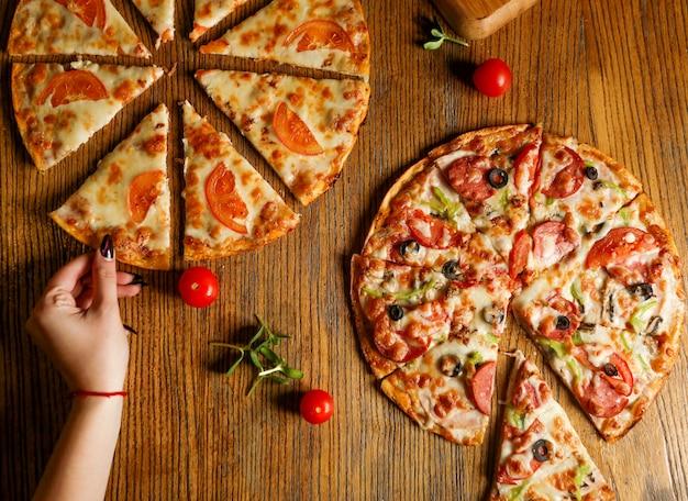Pedaços fatiados de pizza mista com linguiça e pizza com queijo e tomate