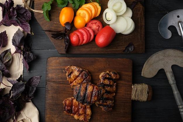 Pedaços grelhados de carne de porco, ao lado de uma tábua com legumes frescos picados