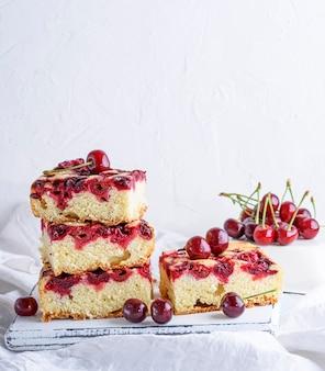 Pedaços quadrados cozidos de uma torta de biscoito com cerejas