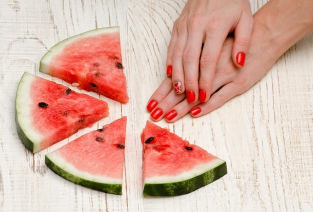 Pedaços triangulares de melancia e mãos de mulher com uma manicure