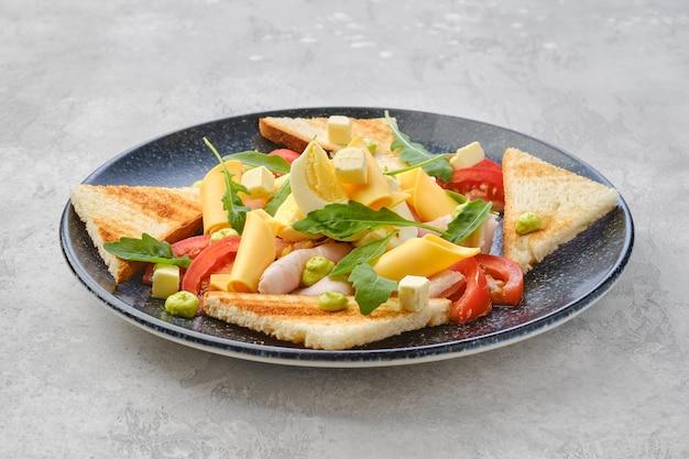 Pedaços triangulares de torrada, presunto, ovo cozido, queijo cheddar e tomate