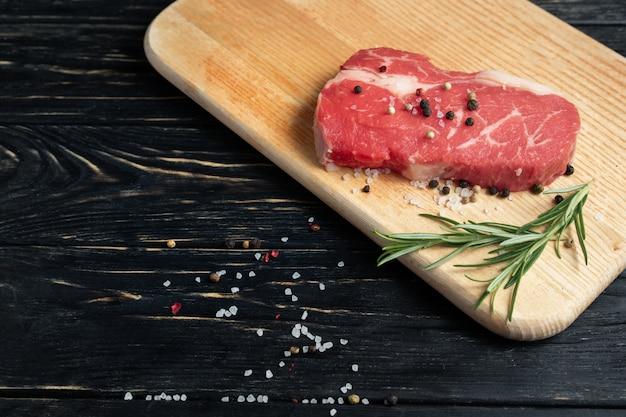 Pedaços um de carne crua suculenta em uma placa de corte em um fundo de mesa de madeira preto.