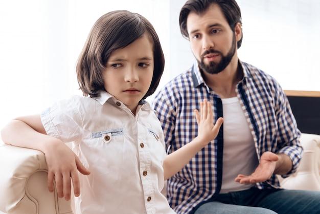 Pede perdão do filho ofendido na sala de estar.