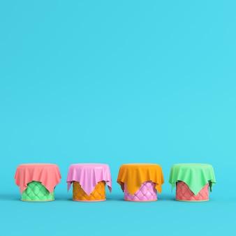 Pedestais costurados cobertos por tecido com moldura redonda sobre fundo azul brilhante em cores pastel