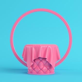 Pedestal bordado rosa coberto por tecido com moldura redonda em fundo azul brilhante em cores pastel