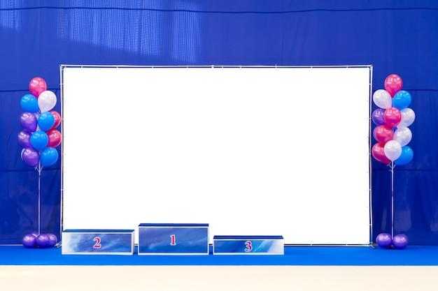 Pedestal de vencedores ou pódio com balões coloridos dentro do ginásio ou salão. quadro vazio de espaço livre.
