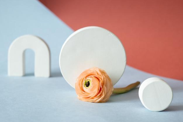 Pedestal em forma de círculo de concreto branco e flor rosa em um vaso sobre fundo azul de papel pastel. plataforma de pedra.