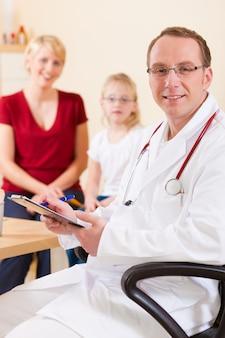 Pediatra com a família em sua cirurgia