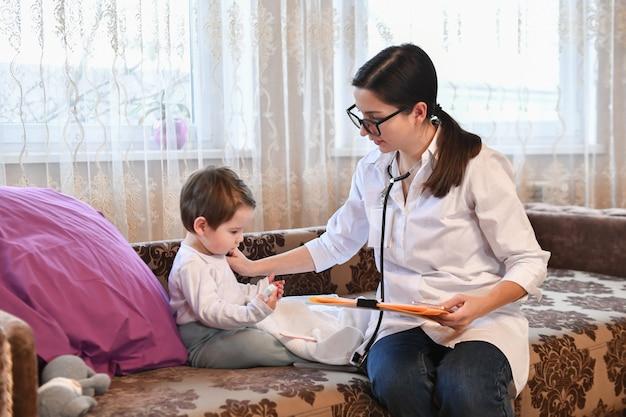 Pediatra com um paciente pequeno em casa. inspeção do bebê
