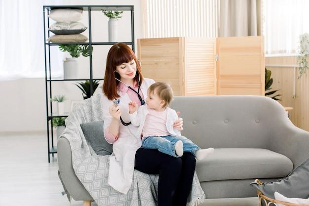 Pediatra da mulher profissional que examina o bebê pequeno pelo estetoscópio. médico e bebê sentado no sofá cinza na clínica moderna