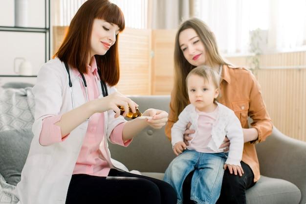 Pediatra dando um xarope para menina doente sentado com a mãe e mostra a dosagem