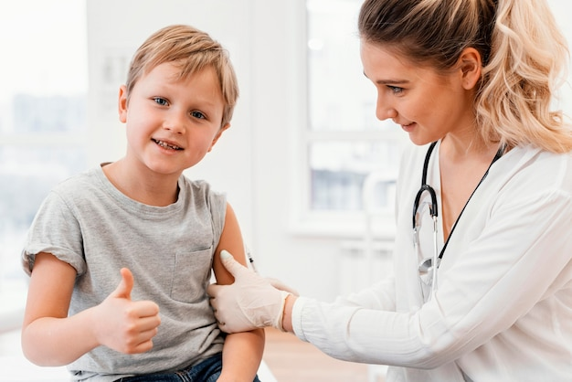Pediatra de close-up vacinando criança