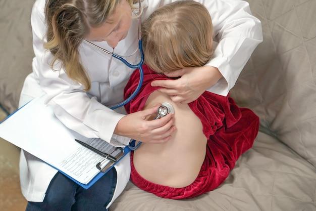 Pediatra examina o coração de uma menina