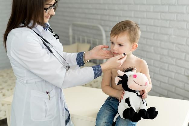 Pediatra examinando glândula tireoide de menino na clínica