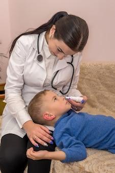 Pediatra fazendo cair o nariz para o pequeno paciente na clínica