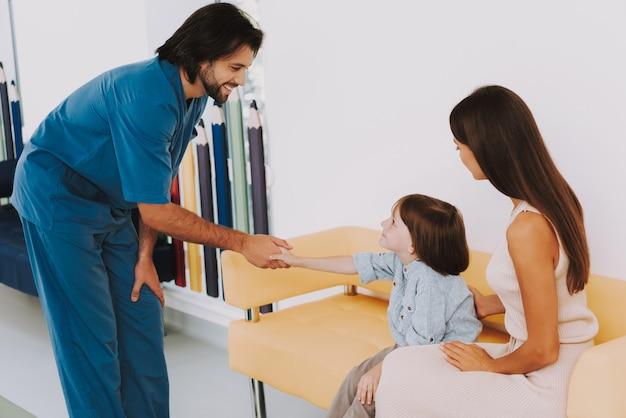 Pediatra feliz cumprimenta garoto garotinho sorrindo