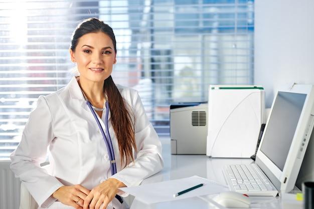 Pediatra feminina sentada no local de trabalho, posando, sorrindo, tendo o estetoscópio no pescoço. medicina e conceito de saúde
