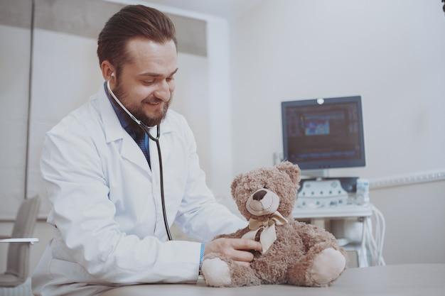 Pediatra masculino amigável que trabalha em sua clínica, fingindo examinar o brinquedo do urso de peluche