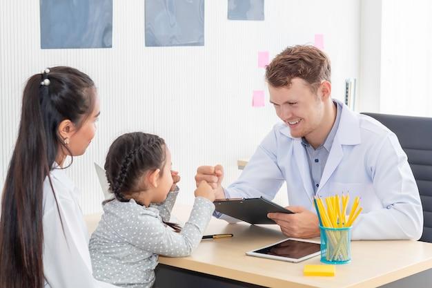 Pediatra (médico) homem dando colisão do punho (cinco altos para), tranquilizando e discutindo a criança na cirurgia. mãe caucasiana e criança sorrindo no quarto do hospital.