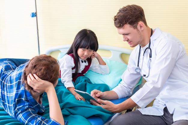 Pediatra (médico) homem gravando e levando informações para tablet com menina paciente e mãe no hospital.