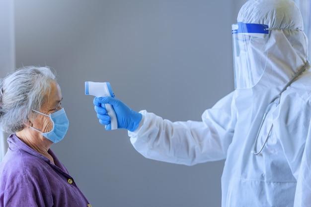 Pediatra ou médico verifica a temperatura corporal de uma mulher asiática idosa elementar usando o termômetro infravermelho para a testa para vírus.