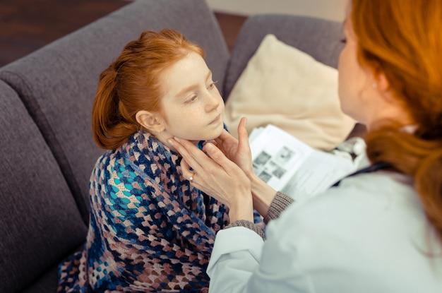 Pediatra profissional. mulher agradável e agradável tocando o pescoço da menina enquanto verifica seu estado de saúde