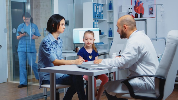 Pediatra que redige receita para criança após exame. profissional de saúde, médico, especialista em medicina na prestação de serviços de saúde, consulta, tratamento diagnóstico em hospital.
