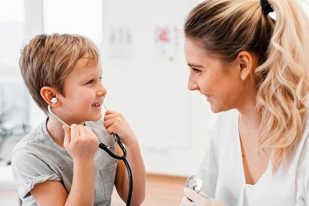 Pediatra sorridente de close-up e criança