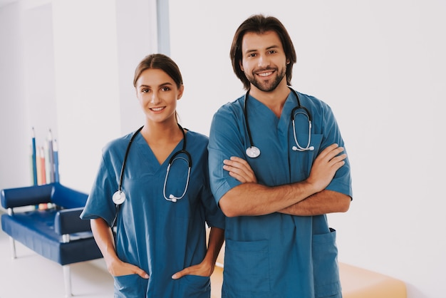 Pediatras amigáveis em uniforme azul no corredor