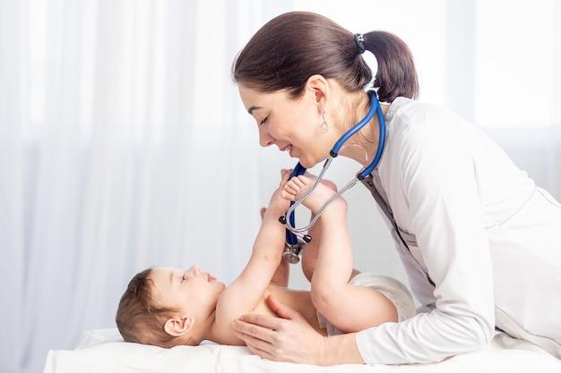 Pediatria, um médico examina um menino e usa um estetoscópio para ouvir os batimentos cardíacos ou a respiração do bebê, o conceito de medicina e saúde