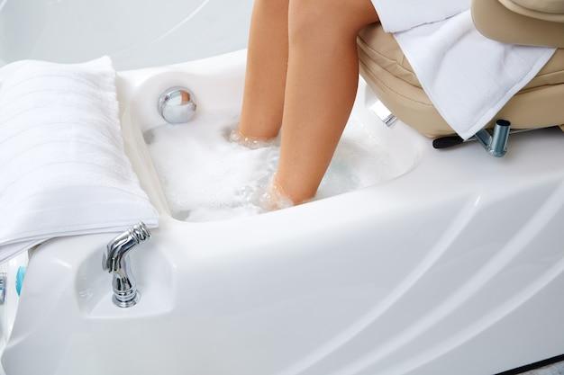 Pedicure banho de pés na cadeira do sofá no salão de unhas