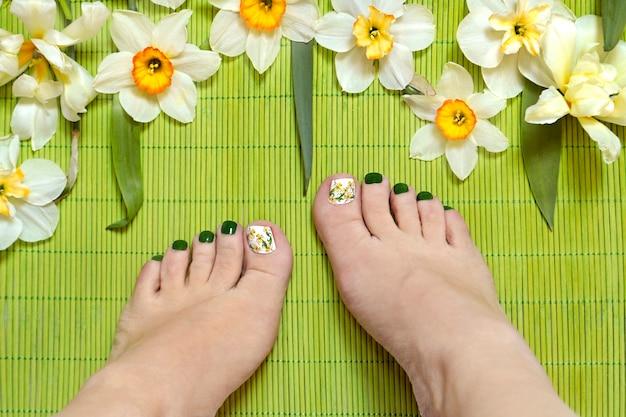 Pedicure com esmalte verde e controle deslizante com narcisos