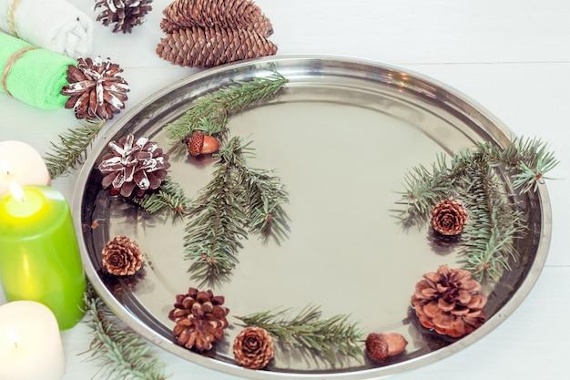 Pedicure e manicure de coníferas no salão spa com ramos de abeto e cones em um fundo branco de madeira