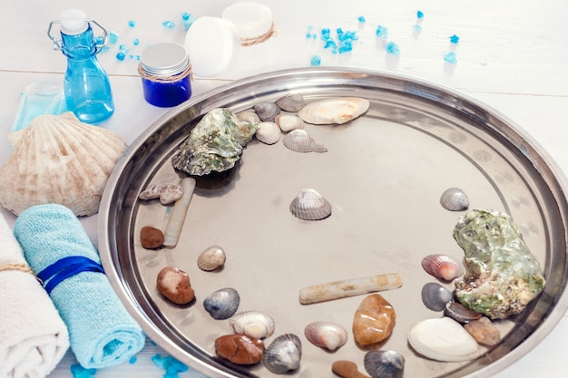 Pedicure e manicure no salão spa com conchas e pedras em um fundo branco de madeira