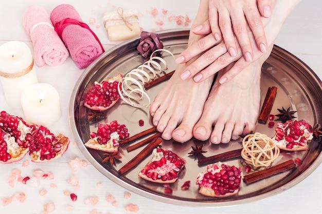 Pedicure e manicure no salão spa com romã, canela e anis em uma mesa de madeira branca