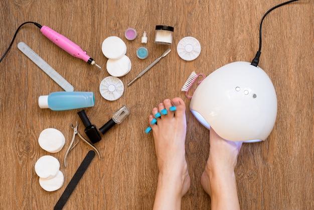 Pedicure em casa usando esmalte e lâmpadas uv, limas de unha e tesoura