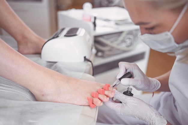 Pedicure fazendo esmalte branco nas pernas do cliente usando lâmpada shellac