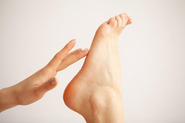Pedicure francês da mulher. close-up mãos de mulher tocando pernas longas